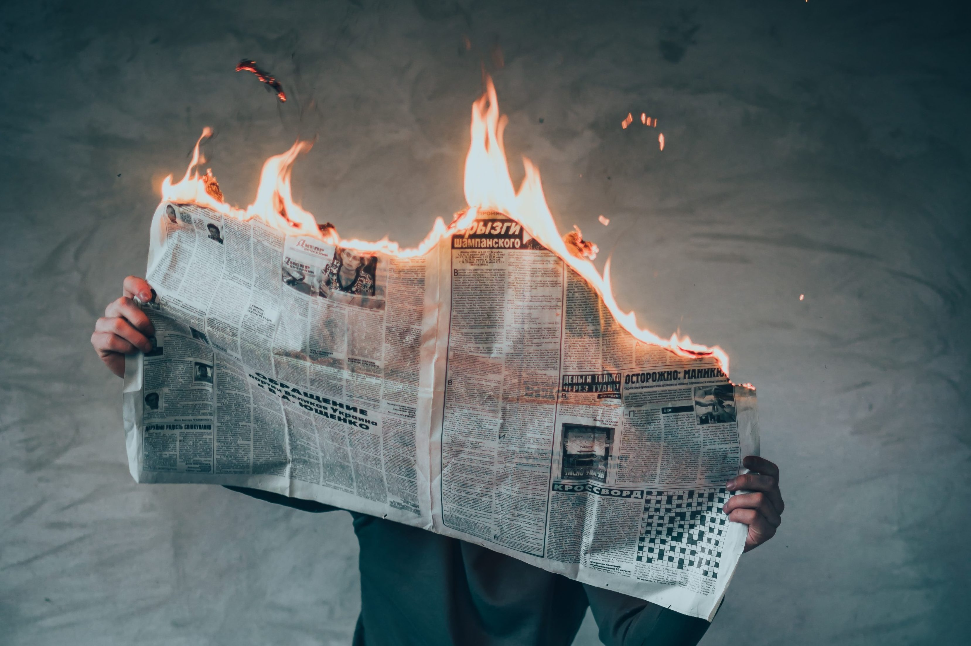 A man reads a newspaper that is on fire while standing against a wall