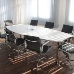 An empty white conference table sits in a room during late afternoon