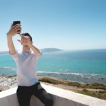 A man takes a selfie on the roof of a white building with a sunny beach in the background