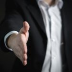 a man in a business suit extends his arm for a handshake at the beginning of a business relationship